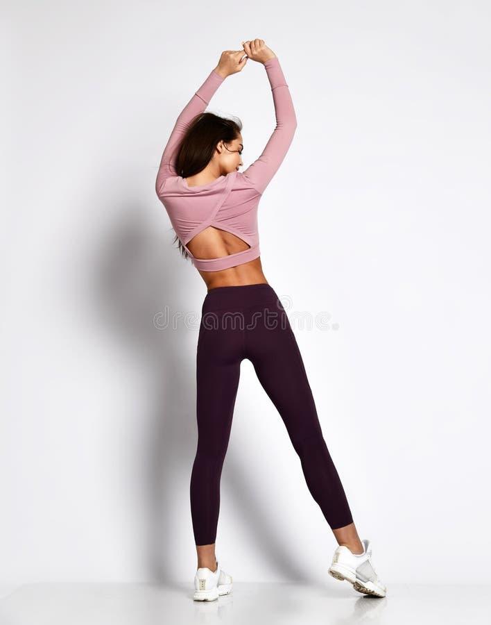 Het sexy atletische vrouwen sportieve meisje in de kleren van de maniersportkleding bevindt zich stellend na trainingoefeningen royalty-vrije stock foto