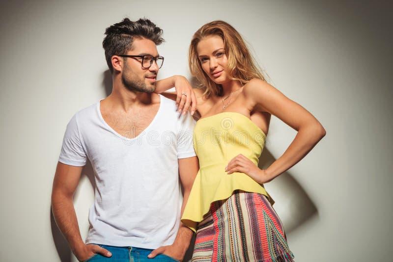 Het sexy blondemeisje stellen terwijl boyfrend van hem houdt dient zak in stock fotografie