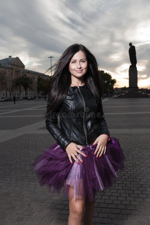 Het sexy brunette weared in openlucht zwart leerjasje stock foto's