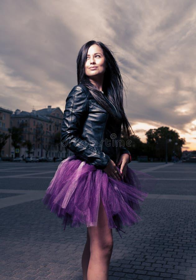 Het sexy brunette weared in openlucht zwart leerjasje royalty-vrije stock afbeelding