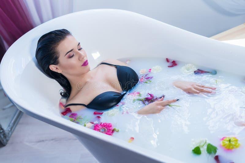 Het sexy donkerbruine vrouw ontspannen in een heet bad met bloemen royalty-vrije stock afbeeldingen
