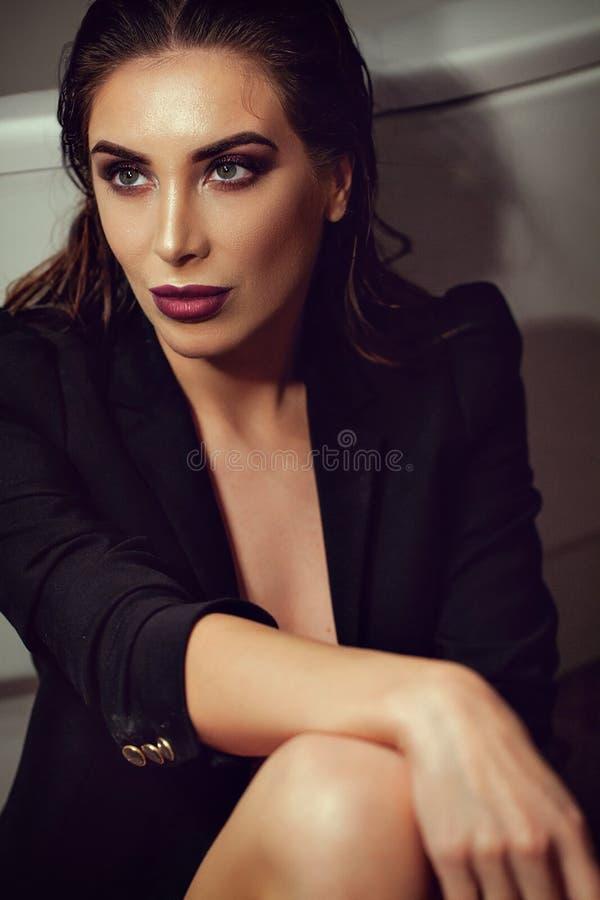 Het sexy donkerbruine vrouw stellen in leunstoel in modieuze zwarte kleding royalty-vrije stock foto's
