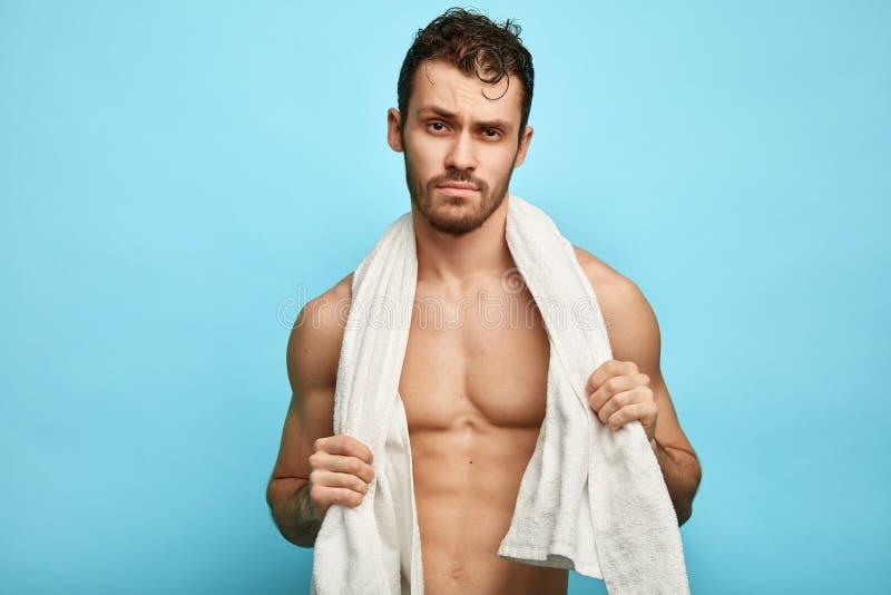 Het sexy ernstige naakte gebaarde kerel stellen aan de camera na het zwemmen royalty-vrije stock afbeelding