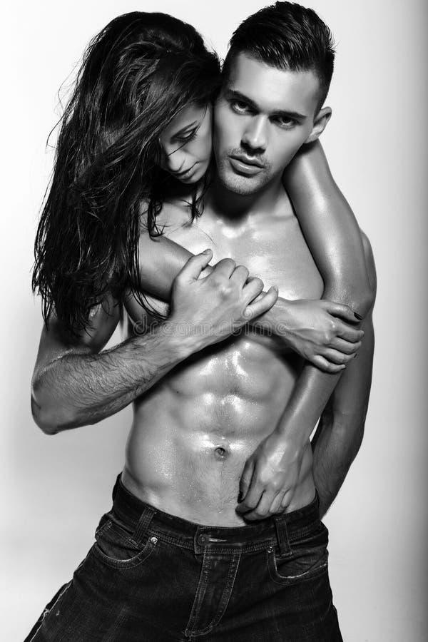 Het sexy gloedvolle paar stellen in studio stock fotografie