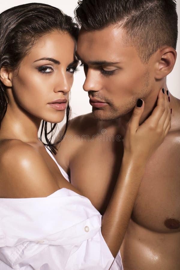 Het sexy gloedvolle paar stellen in studio stock afbeeldingen