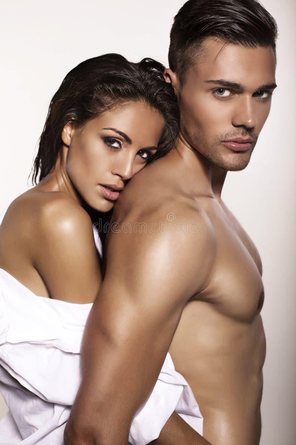 Het sexy gloedvolle paar stellen in studio stock afbeelding