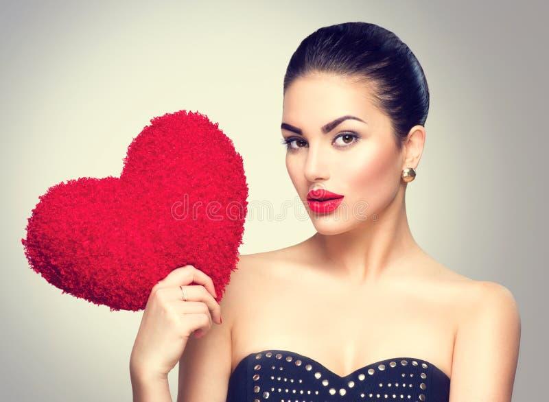 Het sexy hart van de vrouwenholding vormde rood hoofdkussen stock afbeelding