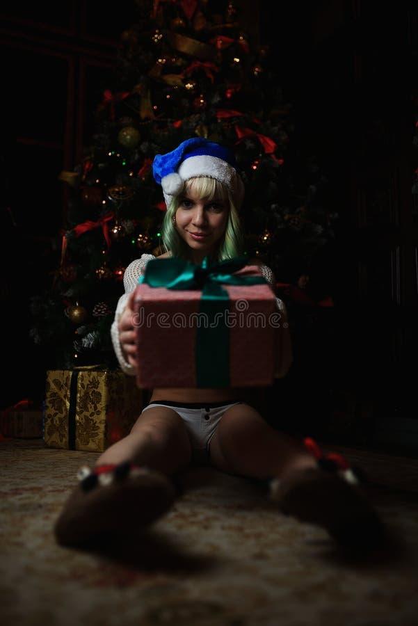 Het sexy jonge meisje heeft gift onder Kerstboom ontvangen stock fotografie