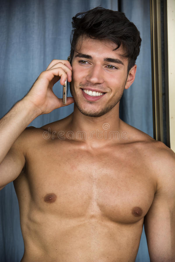 Het sexy jonge mens shirtless spreken op telefoon stock foto's