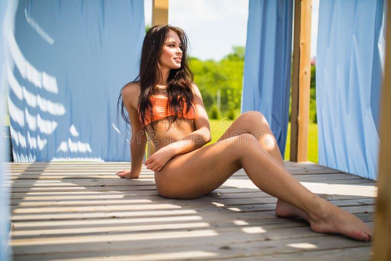 Het sexy jonge vrouw liggende ontspannen op ligstoel dichtbij pool stock afbeeldingen