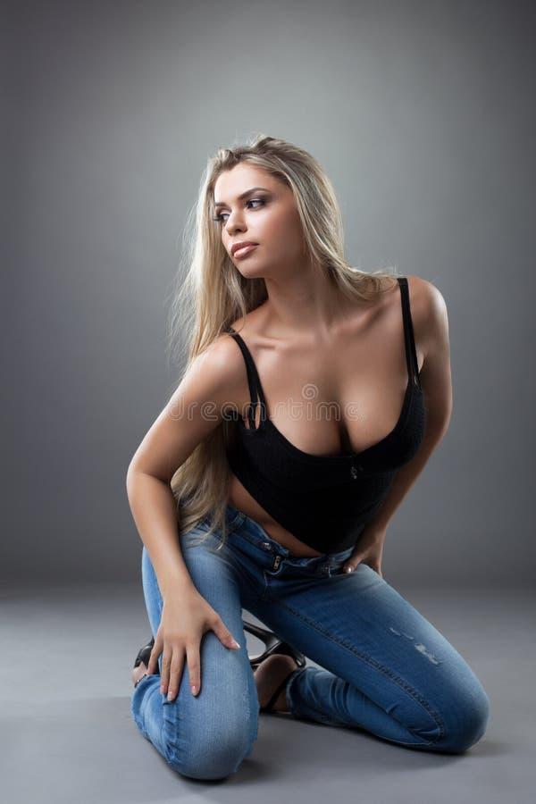 Het sexy jonge vrouw stellen in zwarte en jeans stock fotografie