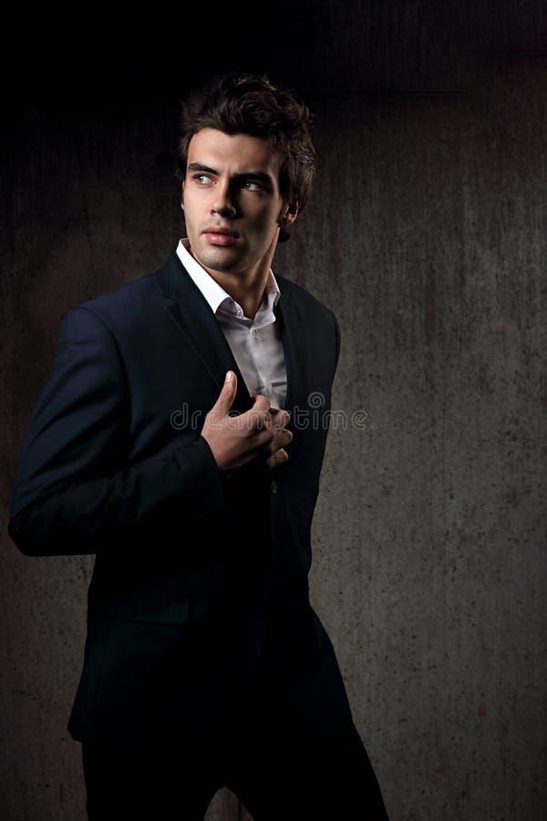 Het sexy knappe mannelijke model stellen in blauw manierkostuum en wit s royalty-vrije stock afbeeldingen