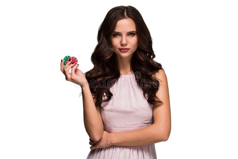 Het sexy krullende haar donkerbruine stellen met spaanders in haar handen, de isolatie van het pookconcept op witte achtergrond stock afbeelding