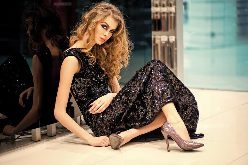 Het sexy meisje in avondjurk zit op vloer, manier royalty-vrije stock foto