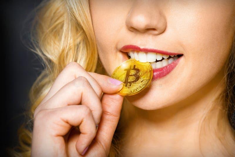 Het sexy meisje houdt een gouden muntstuk bitcoin dichtbij de mond royalty-vrije stock fotografie