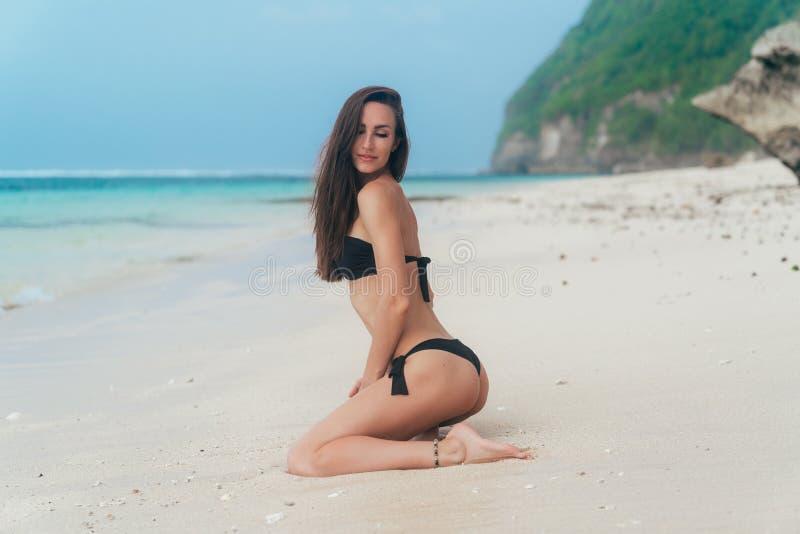 Het sexy meisje met sportief lichaam in zwarte bikini stelt op strand met blauwe oceaan bij achtergrond stock afbeelding