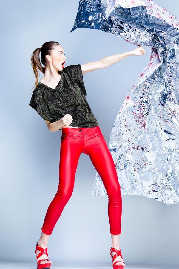 Het sexy model met slank lichaam kleedde zich in het rode stellen in de studio stock fotografie