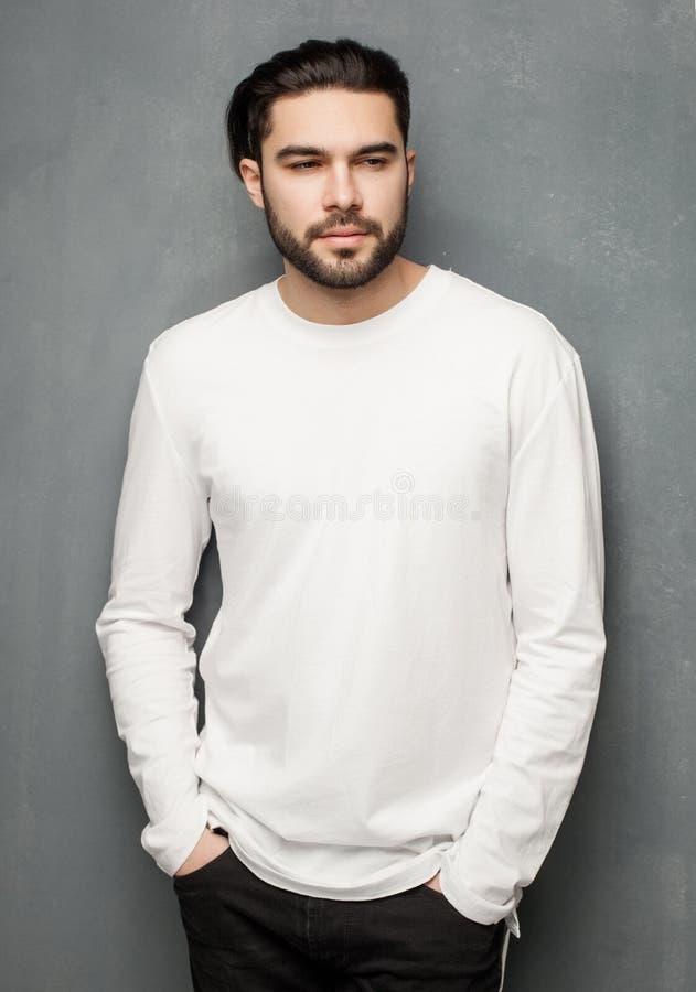 Het sexy model van de maniermens in het witte sweater, jeans en laarzen dramatisch stellen stock afbeeldingen