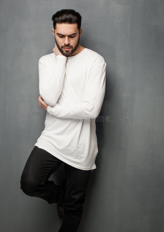 Het sexy model van de maniermens in het witte sweater, jeans en laarzen dramatisch stellen stock afbeelding
