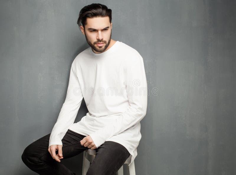 Het sexy model van de maniermens in het witte sweater, jeans en laarzen dramatisch stellen stock foto
