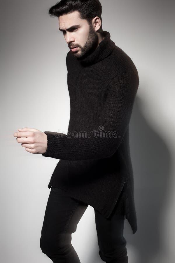 Het sexy model van de maniermens in het zwarte sweater, jeans en laarzen dramatisch stellen stock foto's