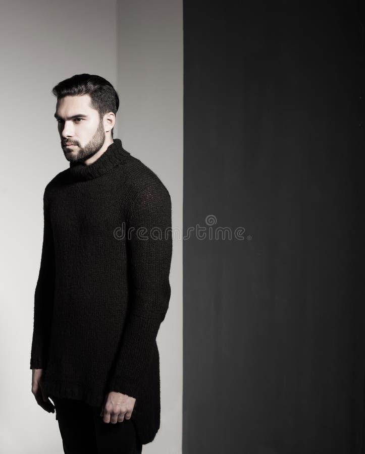 Het sexy model van de maniermens in het zwarte sweater, jeans en laarzen dramatisch stellen stock foto