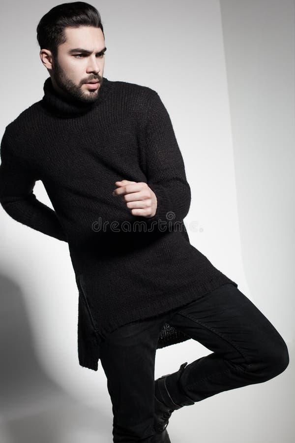 Het sexy model van de maniermens in het zwarte sweater, jeans en laarzen dramatisch stellen stock fotografie
