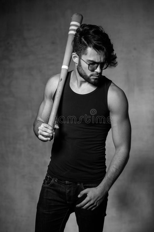 Het sexy model van de maniermens met honkbalknuppel stellen dramatisch tegen grungemuur stock afbeeldingen