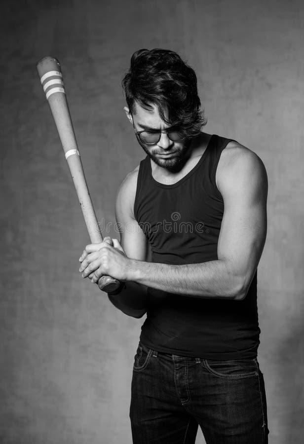 Het sexy model van de maniermens met honkbalknuppel stellen dramatisch tegen grungemuur royalty-vrije stock afbeelding