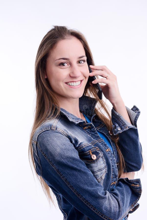 Het sexy mooie jonge vrouw model stellen in een studio met mobiele telefoon en blauw denimjasje stock fotografie