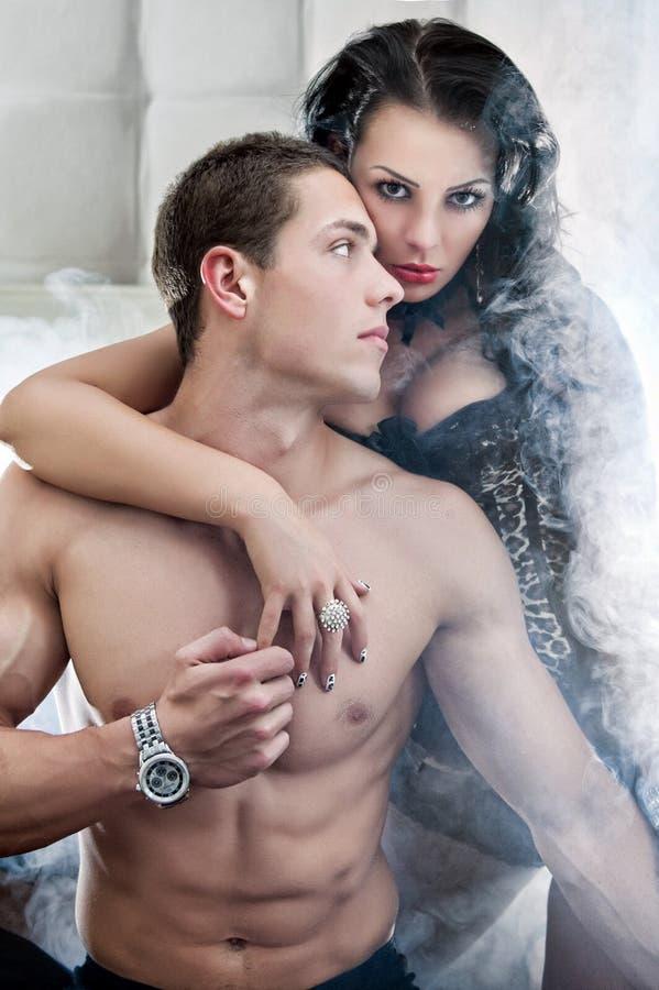 Het sexy paar in romantisch stelt in bed stock afbeeldingen