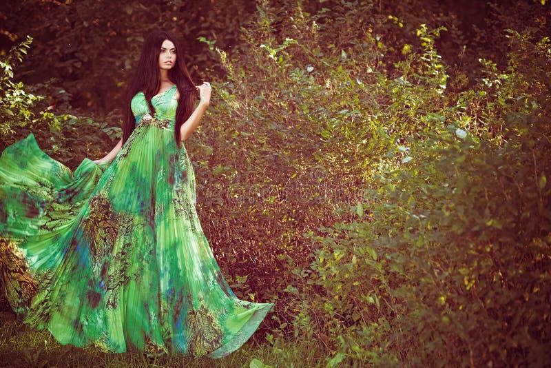Het sexy sensuele zeer mooie meisjesbrunette in groene kleding kijkt t stock foto