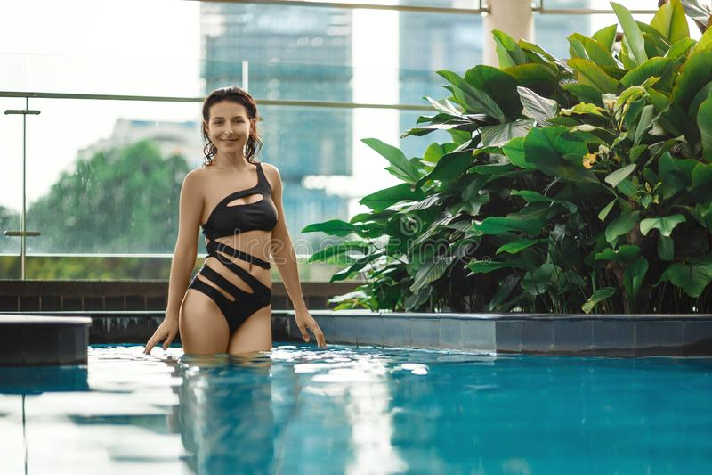 Het sexy slanke vrouwelijke stellen tussen groene installaties in pool op dak met cityscape Luxevakantie in Azië stock afbeelding