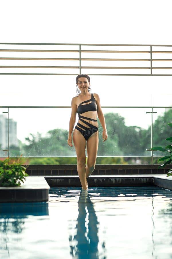 Het sexy slanke vrouwelijke stellen tussen groene installaties in pool op dak met cityscape Luxevakantie in Azi? royalty-vrije stock foto