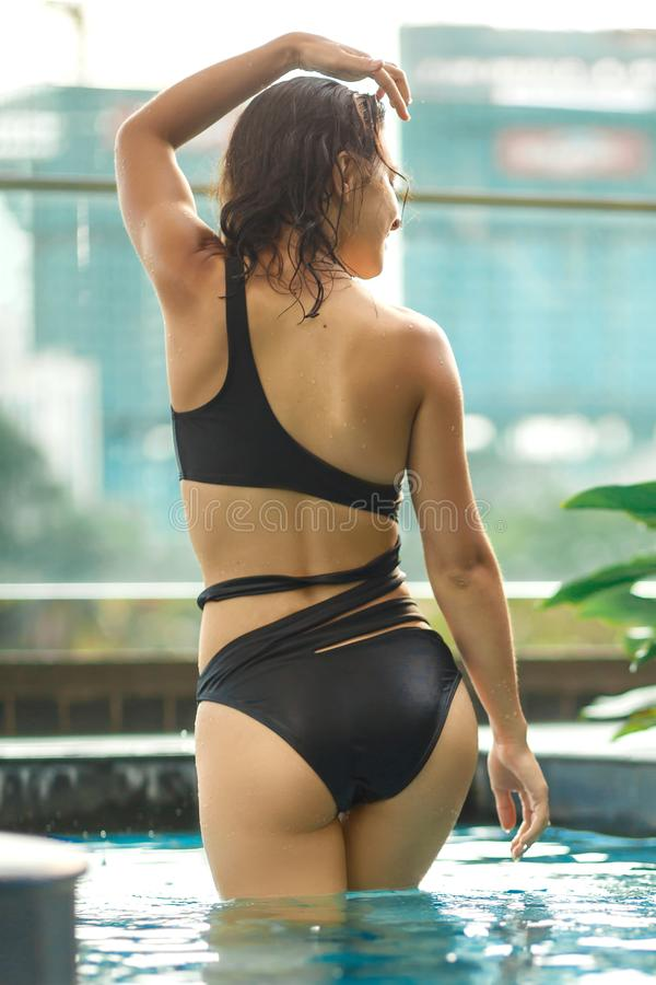Het sexy slanke vrouwelijke stellen tussen groene installaties in pool op dak met cityscape Luxevakantie in Azi? stock fotografie