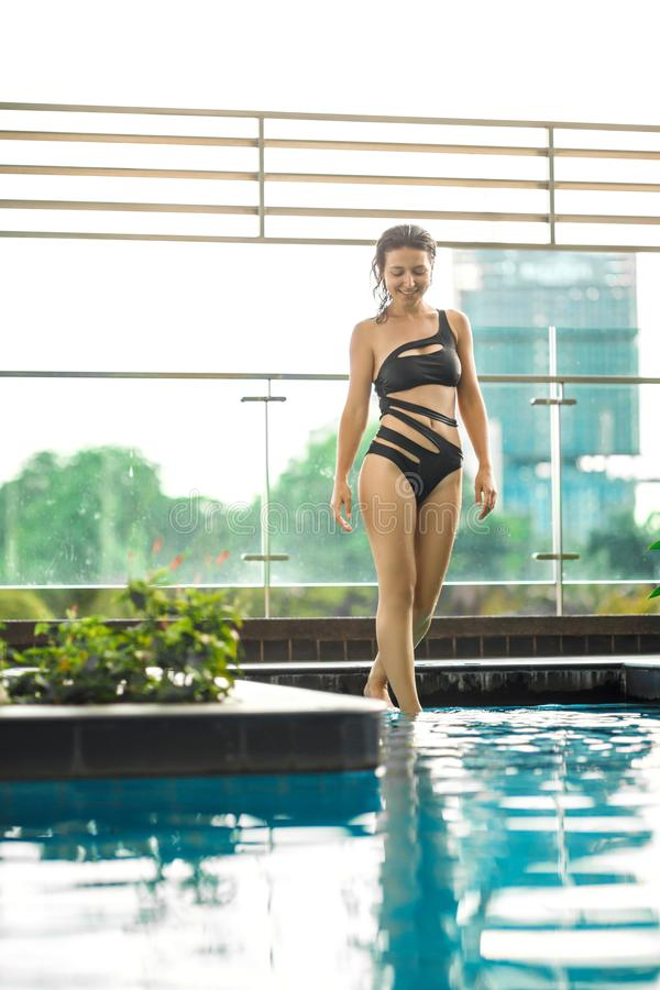 Het sexy slanke vrouwelijke stellen tussen groene installaties in pool op dak met cityscape Luxevakantie in Azi? royalty-vrije stock fotografie