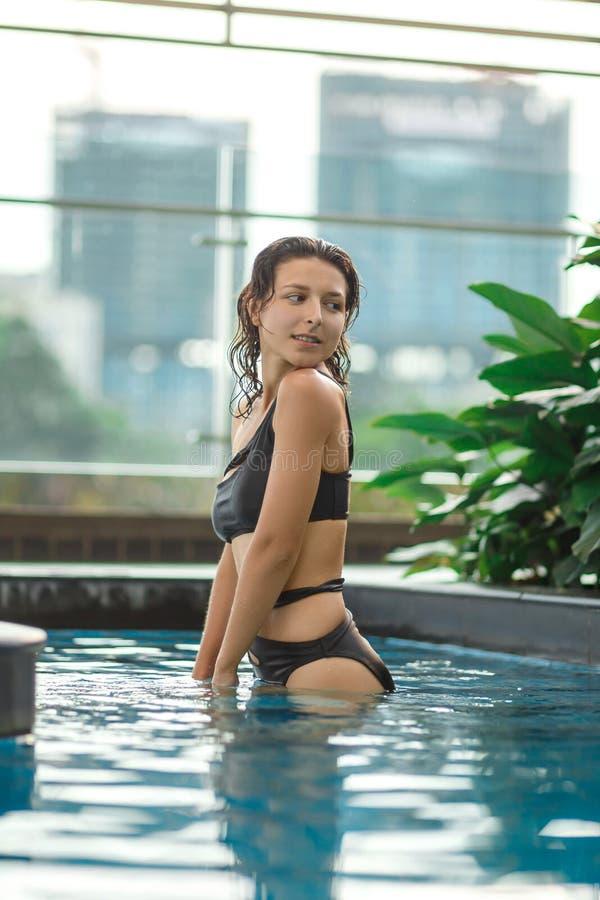 Het sexy slanke vrouwelijke stellen tussen groene installaties in pool op dak met cityscape Luxevakantie in Azi? royalty-vrije stock foto's