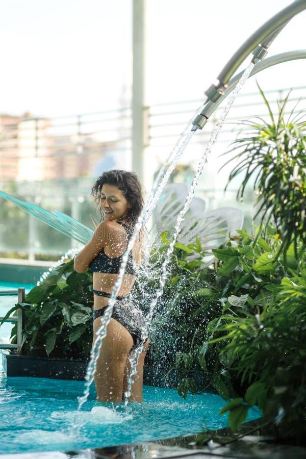 Het sexy slanke wijfje in zwempak neemt douche in zwembad tussen groene struiken op dak met stads scape achtergrond stock afbeeldingen