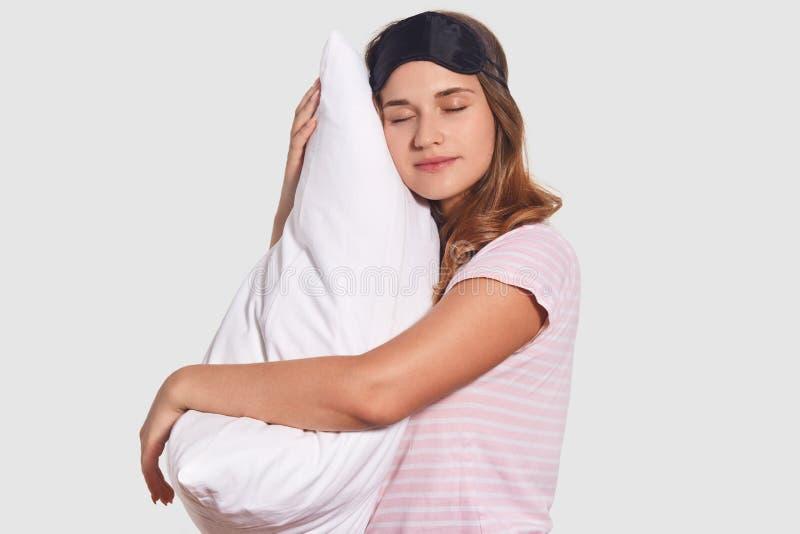 Het Siewaysschot van ontspannen Kaukasische vrouw neemt dutje op zacht hoofdkussen, draagt slaapmasker, heeft goede rust na harde stock foto