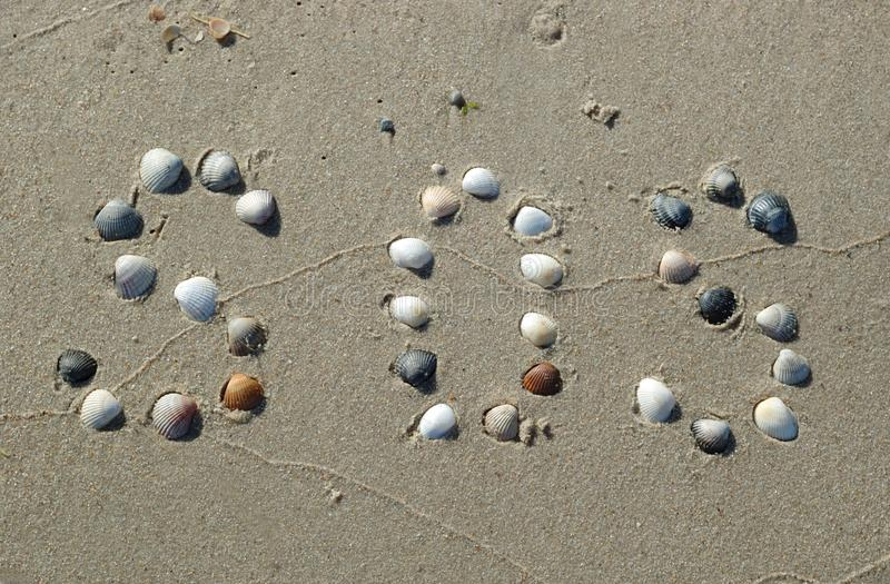 S.O.S.signaal op het zand van shells wordt gemaakt die