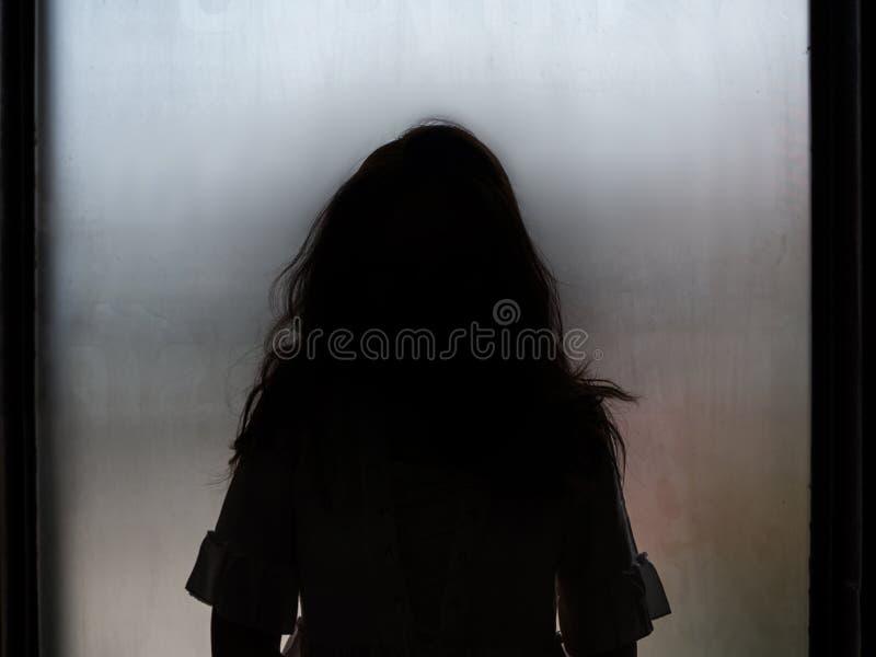 Het silhouet die van het spookmeisje zich voor venster bevinden royalty-vrije stock foto's