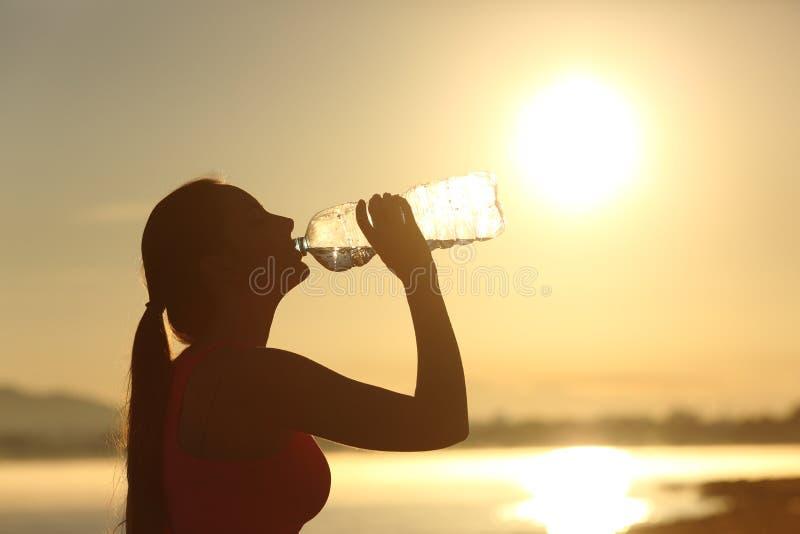 Het silhouet drinkwater van de geschiktheidsvrouw van een fles stock afbeeldingen