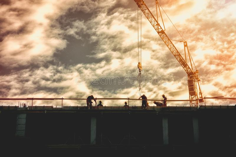 Het silhouet van arbeiders op de bovenkant van de bouwconstructieplaats met kraan en zonsondergangzonlicht, beeld bevat filmgrain stock foto's