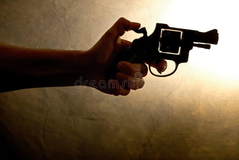 Het silhouet van a bemant hand met een pistool royalty-vrije stock afbeeldingen