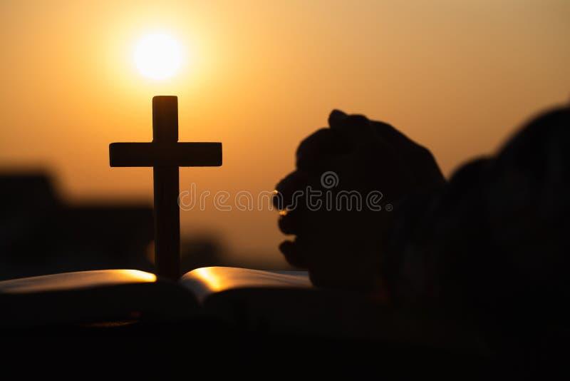 Het silhouet van het christelijke jonge vrouw bidden met dwars en opent de bijbel bij zonsopgang, Christian Religion-conceptenach stock afbeeldingen