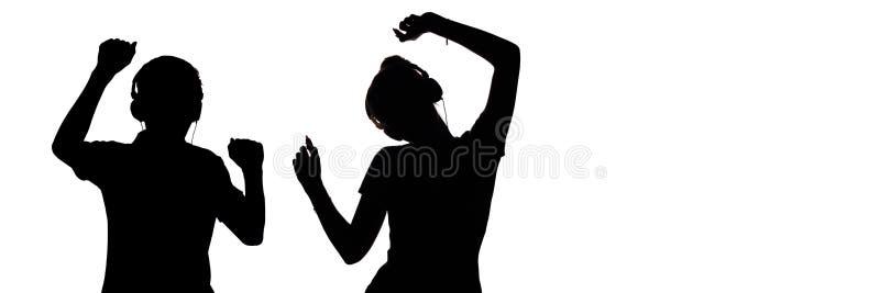 Het silhouet van cijfers van tieners in hoofdtelefoons die aan muziek luisteren, de kerel en het meisje dansen met omhoog handen, stock afbeeldingen