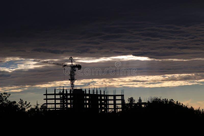 Het silhouet van de bouwkraan in de wolken royalty-vrije stock afbeeldingen