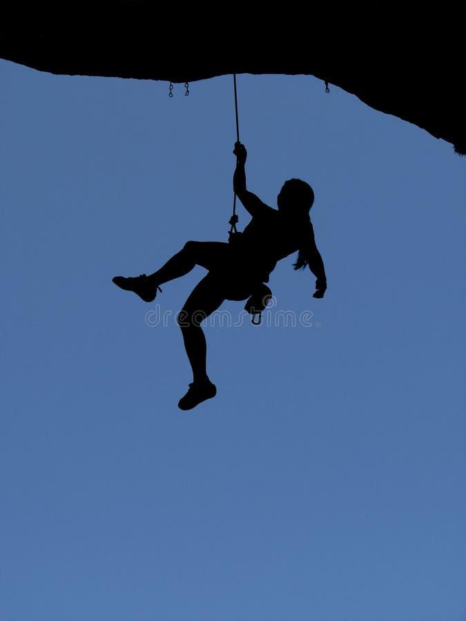 Het silhouet van de de rotsklimmer van de vrouw stock foto