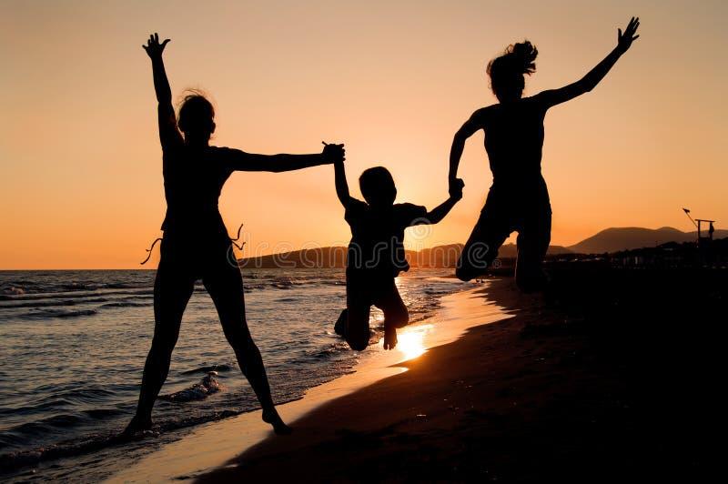 Het silhouet van de familie op het strand royalty-vrije stock afbeelding