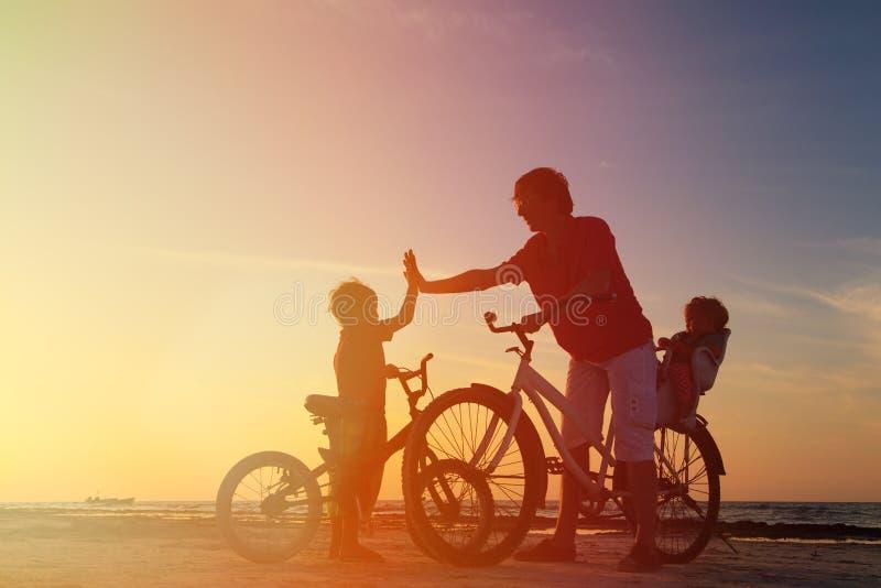 Het silhouet van de fietserfamilie, vader met twee jonge geitjes  royalty-vrije stock foto